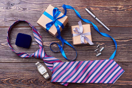 Gift boxes and wrist clock. Tie near cufflinks and pen. Create an elegant look.