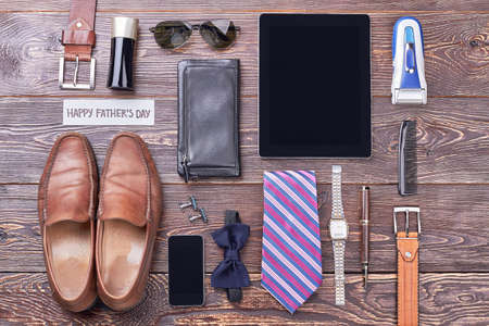 Fathers Day card near accessories. Cologne, tablet and sunglasses. Modern mens fashion trends. Stock Photo
