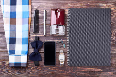 consist: Paper notepad and accessories. Shirt, watch and pen. Success consists of many details.