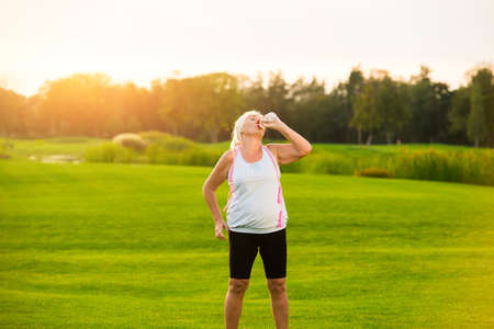 tiredness: Woman drinking water from bottle. Lady standing on green grass. Training is finished. Tiredness and thirst.
