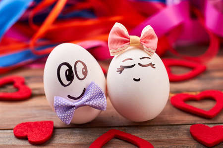 Love eggs and red hearts. Bows on eggs with faces. Art and food.