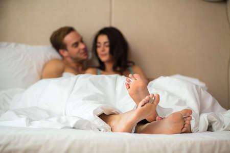 Füße von kaukasischen Paar. Junge Leute im Bett. Verbringen Sie ein Wochenende in Ihrem Zuhause.