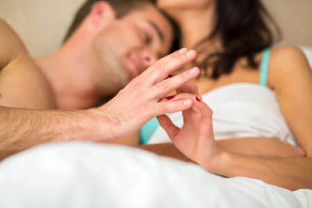 feel affection: Couple touching hands in bed. Young caucasian woman and man. No one can separate us. Stock Photo
