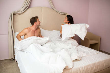 beloved: Couple holding pillows. Young man and woman indoor. Spending weekend with beloved.