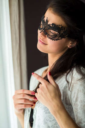 Lady in black lace mask. Woman touching her hair. Dreaming about love.