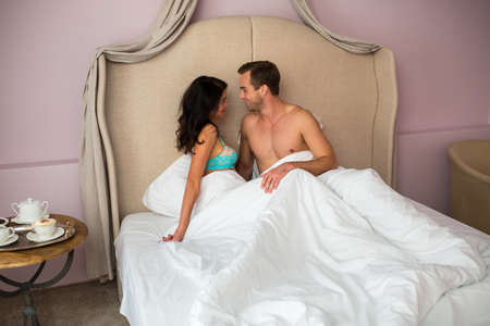belong: Caucasian couple in bed. Smiling man looks at woman. You belong with me.