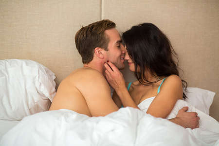 feel affection: Woman with man in bed. Girl touching guys face. Stay here with me.