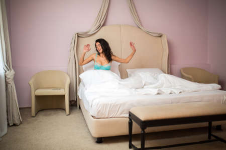 Woman in bed. Young female indoors. Wake up and get dressed. Stock Photo