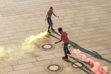 roller blade: Couple is rollerblading. Colorful smoke coming from roller blade. Colorize the world.