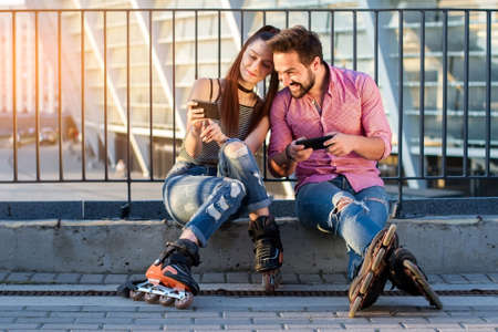 Couple holding cell phones. Two roller blade sitting. Sharing new photos.