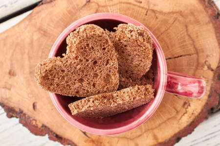 Bread in shape of heart. Pink cup on wooden background. Creative and cute meal.