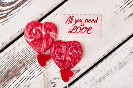 curare teneramente: Lollipops and red hearts. All you need is love. Cherish what you have. Archivio Fotografico