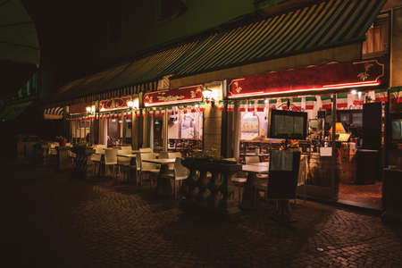 where to eat: Empty restaurant at night. Tables and chairs near windows. Where to eat in Stresa. Stock Photo