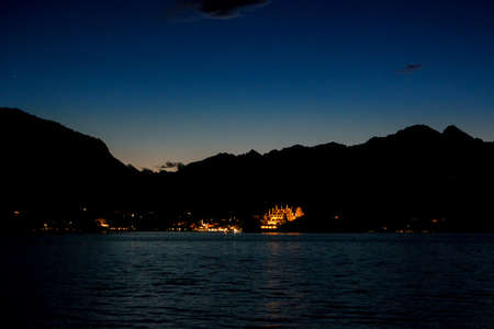 uncover: Sky and mountains at night. Lights of town at distance. Uncover the secrets of island. Stock Photo