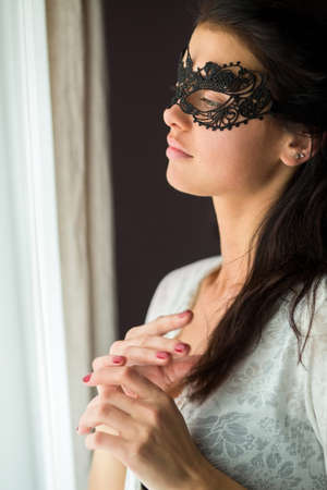 Girl in lace mask. Young woman near window. Sad and lonely.