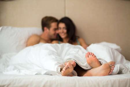 Paare Füße unter Decke. Kaukasischen Frau und Mann innen. Komfort und Romantik.