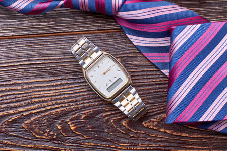 Watch near striped tie. Necktie on wooden surface. Punctuality is important for business. Stock Photo