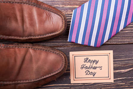 defines: Greeting card, shoes and tie. Necktie on wooden surface. Footwear defines the whole look.