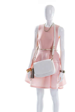 Dress and purse on mannequin. Elegant outfit on female mannequin. White dress belt and purse. Gilded bracelet and leather handbag. Stock Photo