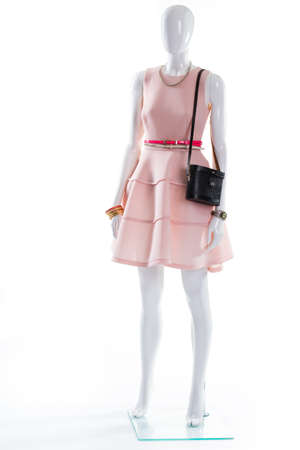 Dress and bijouterie on mannequin. Female mannequin in expensive outfit. Delicate jewelry and stylish accessories. Womans stylish apparel with accessories.