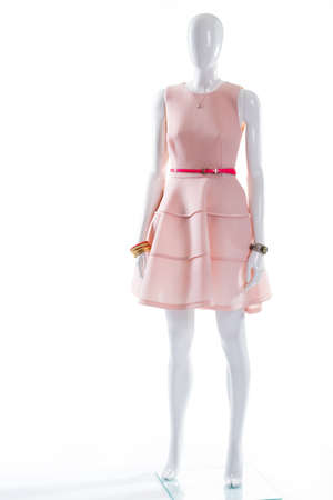 Pink dress belt on mannequin. Female mannequin in glossy belt. Salmon dress with pink belt. Stylish accessories and cocktail dress.