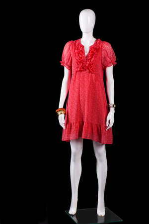Red v-neck summer dress. White mannequin in red dress. Ladys clothing on black background. Seasonal offer at fashion store. Stock Photo