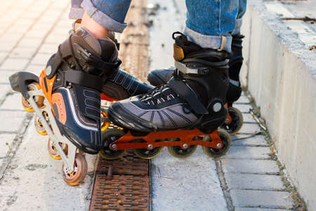 durability: Feet on rollerblades. Orange and black inline skates. High durability and new design.