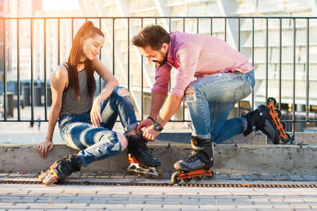 strengthen: Woman and man wearing rollerblades. Guy is helping a girl. Common hobbies strengthen relationships. Stock Photo