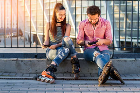 Couple with cell phones. People on rollerblades sitting. Prank your boyfriend.
