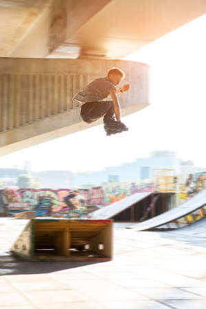off ramp: Guy on rollerblades jumping. Young man rollerblading outdoors. Jump off the ramp. Stock Photo