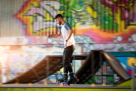 Young male rollerblading. Person near graffiti. Speed and precision of moves. Stock Photo