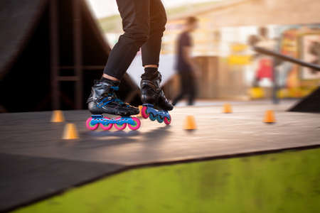 skate park: Legs of person rollerblading. Black skates with pink wheels. Be fast and agile.