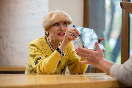 Old lady holding a tablet. Senior woman at the table. New design and improved hardware. Stock Photo