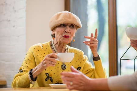Senior lady with cup. Woman in cafe. The attentive listener.