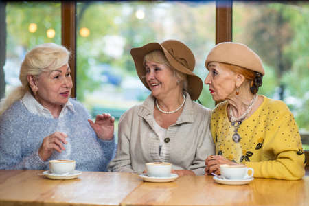 interesting: Three senior ladies at table. Women near cafe window. Tasty coffee and interesting conversation.