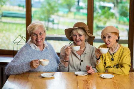 Women with coffee smiling. Three happy senior ladies. Old friends meet in cafe. Zdjęcie Seryjne