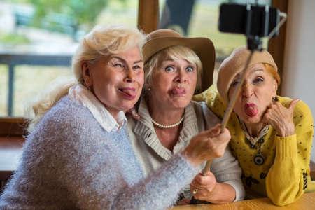Drie dames nemen selfie. Senior vrouwen tonen tong. Gek rond als kinderen.