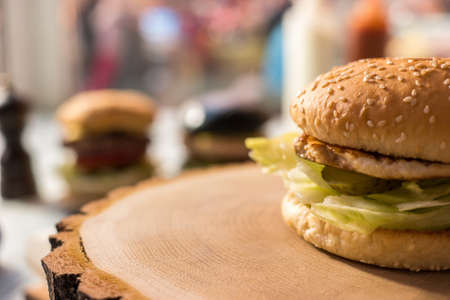 pickle: Hamburger on wooden board. Meat and slice of pickle.
