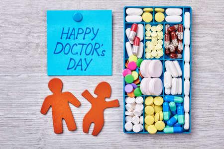stickmen: Medicine in container. Stickmen on wooden surfice. Congratulation for a doctor. Stock Photo