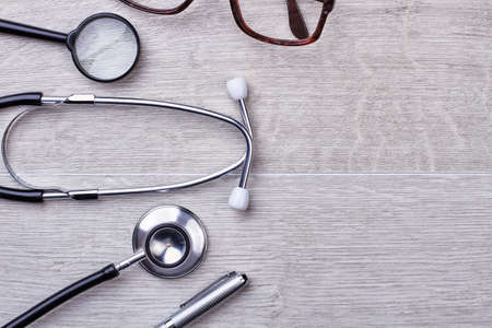 Glasses, magnifier and stethoscope. Empty space for advertisement.