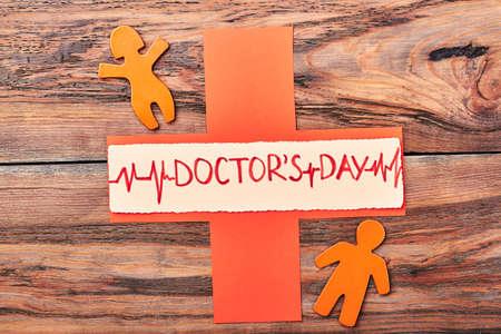 Orange stickmen and cross. Happy Doctors Day to cardiologist. Stock Photo