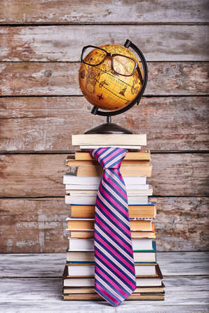 Stack of books and tie. Glasses on globe. Knowledge is a journey.