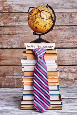 Glasses on globe and tie. Stack of books and card. Congratulate geography teacher. Stock Photo
