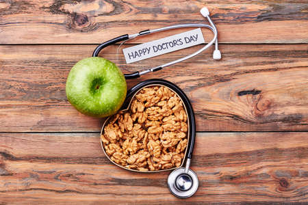 rythm: Walnuts, box, stethoscope and apple. Friendly congratulation to a doctor.