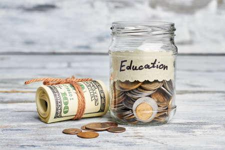 Monedas en contenedor y dólares. La educación es clave para el éxito. Foto de archivo