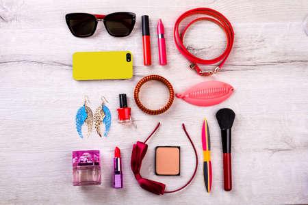 Telefoon, zonnebril en cosmetica. Boog haarband en oorbellen. Maak je stijl af met accessoires. Items van moderne modieuze look.