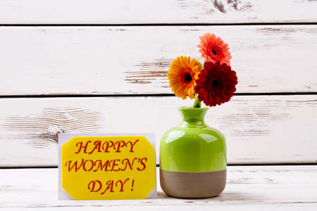 Womens Day card and gerberas. Vase with flowers near card. Spread positive and spring mood. Lovely floral surprise for woman. Stock Photo