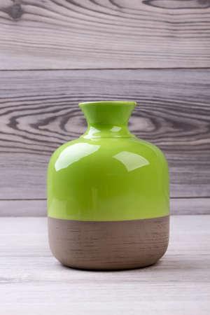 Bicolor vase on wooden background. Ceramic enameled vase. Design of combined colors vase. Handmade modern vase.