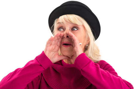 Senior woman is shouting. Female holds hands near mouth. Stock Photo