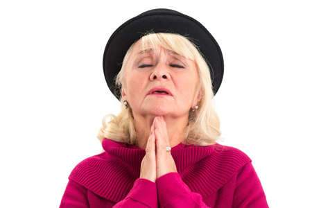 Old lady praying isolated. Senior female with closed eyes. Stock Photo